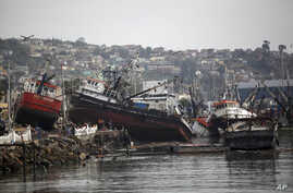 Boats lifted by an earthquake-triggered tsunami sit on a dock, in Coquimbo, Chile, Sept. 18, 2015.
