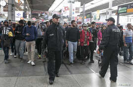 Migrants walk after arriving by train to the main railway station in Munich, Germany, Sept. 6, 2015.