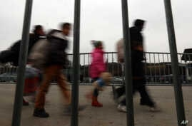 Refugees and migrants are seen walking behind a fence at the border between Slovenia and Austria at Spielfeld, Austria, Feb. 16, 2016.