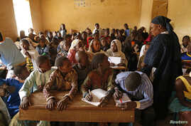Children listen to a school teacher after the reopening of Mahamane Fondogoumo elementary school in the town center of Timbuktu, Mali, February 1, 2013.