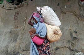 A displaced Somali woman carries a child and her belongings after fleeing famine in the Marka Lower Shebbele regions, as she arrives at a temporary dwelling in the capital Mogadishu.