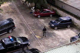 FILE - An unidentified policeman provides security inside the compound of a wealthy Nigerian man, with cars parked ready to provide armed convoys,  and the compound protected by high walls and barbed wire in Port Harcourt, Nigeria, July 27, 2007.