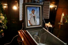 FILE - A picture of slain journalist Gumaro Perez stands on his open casket during a wake inside his mother's home in Acayucan, Veracruz state, Mexico, Dec. 20, 2017.