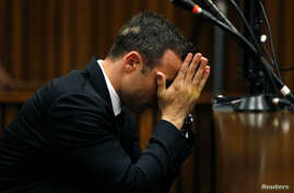Oscar Pistorius reacts in the dock ahead of his trial for the murder of his girlfriend Reeva Steenkamp, at the North Gauteng High Court in Pretoria, March 5, 2014.