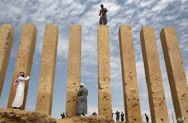 A Yemeni militiaman stands atop a limestone column at the Awwam Temple, Feb. 3, 2018. Experts fear the temple, as well as other historic and cultural wonders across Yemen beyond those acknowledged by international authorities, remain at risk as the c