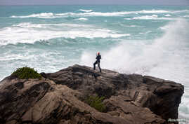 A man takes photos while standing on a cliff on the island's south shore battered by winds from approaching Hurricane Gonzalo, in Astwood Park, Bermuda, Oct. 17, 2014.