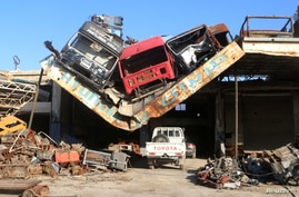 Damaged vehicles pile on a damaged roof of a car mechanic service center in Ramousah area southwest of Aleppo, Syria August 2, 2016.
