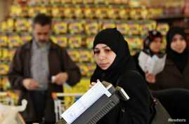 Syrian refugees shop after they receiving humanitarian aid shopping vouchers at a mall in Amman, April 11, 2013.