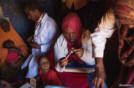 Medical practitioners attend to sick and malnourished children in the drought-stricken Baligubadle village near Hargeisa, the capital city of Somaliland, in this handout picture provided by The International Federation of Red Cross and Red Crescent S
