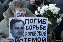 "FILE - A woman holds a placard with a portrait of Sergei Magnitsky during an unauthorized rally in central Moscow December 15, 2012. The placard reads ""Died fighting a system of thievery."""
