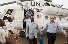 A member of the joint U.N. African Union Mission in Darfur (UNAMID), right, escorts three freed humanitarian workers out of a U.N. helicopter as they landed in El Fasher, North Darfur, Sudan, Saturday, July 19, 2014. The international peacekeeping mi