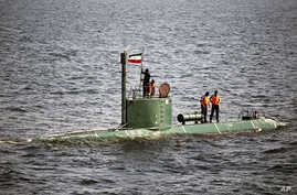 Military personnel place a flag on a submarine during the Velayat-90 war games by the Iranian navy in the Strait of Hormuz in southern Iran December 27, 2011