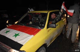 A Syrian driver flies a national flag as people celebrate in the streets in Aleppo, Syria, after the army said it had retaken full control of the city, Dec. 22, 2016. The victory against opposition forces was the army's biggest since the civil war er