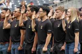 FILE - New Army recruits take part in a swearing in ceremony before a baseball game between the San Diego Padres and the Colorado Rockies in San Diego, June 4, 2017. The Army has missed its recruiting goal for the first time in more than a decade.
