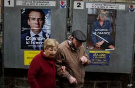 People walk past election posters near a polling station in Paris, France, May 7, 2017. With parliamentary elections looming, mainstream leftists and rightists now struggle to adjust to new political landscape created by a centrist candidate's victor