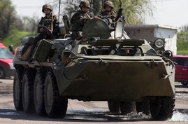 Ukrainian security personnel ride on top of an armoured personnel carrier at a checkpoint near the town of Slovyansk in eastern Ukraine, May 4, 2014.