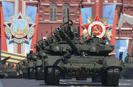 FILE - A Russian serviceman aboard a tank salutes during the Victory Day parade in Moscow's Red Square May 9, 2014.