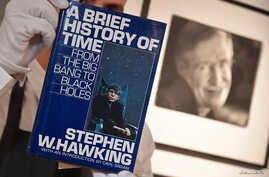 Fine-art handler Tom Richardson poses with a copy of A Brief History of Time which, has a thumb-print inside by author British theoretical physicist Stephen Hawking, ahead of an auction of items from Hawkinsg' personal estate at Christie's in London,