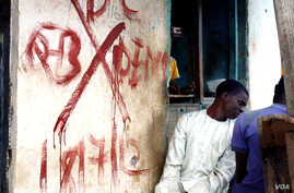"""This building, like most in in Mpape, a settlement inside the Nigerian capital, is marked for demolition with a red """"X."""" Residents say since the buildings were marked, crime has gone up and many families have already moved out. (H. Murdock/VOA)"""