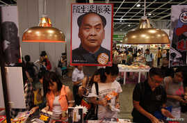 "FILE - Book lovers read beneath poster promoting ""Stange Leung Chun-ying,"" which depicts the new Hong Kong Chief Executive as the late Chinese leader Mao Zedong, Hong Kong Book Fair, July 18, 2012."