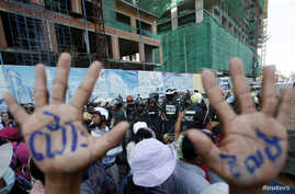 "A man, with his hands painted with words that translate to ""Release"", demonstrate to demand the release of five opposition members of parliament, as police officers block a street near the Phnom Penh Municipal Court in central Phnom Penh, Cambodia, J"