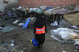 A health worker visits Lahore's slums to administer the polio vaccine to infants, Pakistan, December 19, 2012.