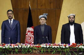 In this photo released by Afghanistan's Presidential Palace, President Ashraf Ghani, center, stands at attention for the national anthem during a joint meeting of the National Assembly in Kabul, Afghanistan, April 25, 2016.