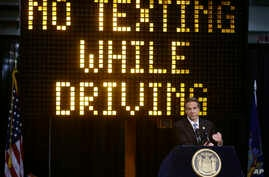 FILE - A sign warns drivers not to text while driving.