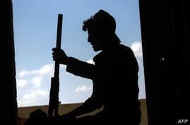 FILE - A member of the Kurdish People's Protection Units (YPG) holds a weapon in the Syrian city of Raqqa June 21, 2017, during an offensive by US-backed fighters.
