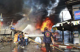 Rescue workers extinguish a fire at the site of a bomb blast in southern Thailand's Yala province, April 6, 2014.