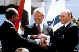FILE - In this March 26, 1979 file photo, Egyptian President Anwar Sadat, left, U.S. President Jimmy Carter, center, and Israeli Prime Minister Menachem Begin clasp hands on the North Lawn of the White House as they completed signing of the peace tre