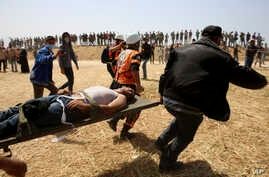 Palestinian protesters and civil defense evacuate a wounded youth during clashes with Israeli troops along Gaza's border with Israel, east of Khan Younis, April 6, 2018.