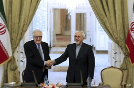 Iranian Foreign Minister Mohammad Javad Zarif, right, shakes hands with U.N. and Arab League envoy on Syria Lakhdar Brahimi as they arrive at their joint press conference in Tehran, Oct. 26, 2013.