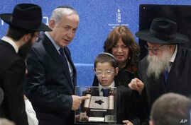 Prime Minister Netanyahu receives a memento from a young boy whose parents were killed during a terror attack as he unveils plans for a state-of-the-art Living Memorial in commemoration of the victims of the Mumbai attacks at the Chabad House in Mumb