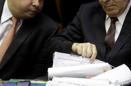 FILE - Brazil's Lower House President Rodrigo Maia and Brazil's Chief of Staff Eliseu Padilha looks at signatures used by Federal deputies of opposition in protest against the pension reform during an opening session of the Year of the Legislative, i