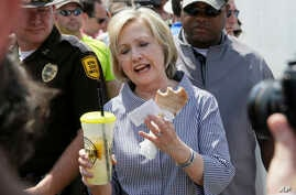 Democratic presidential candidate Hillary Clinton samples a pork chop and a lemonade during a visit to the Iowa State Fair in Des Moines, Aug. 15, 2015.