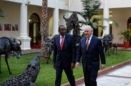 U.S. Secretary of State Rex Tillerson, right, walks with Kenya's President Uhuru Kenyatta, left, past metal sculptures of animals, inside State House in Nairobi, Kenya, March 9, 2018.