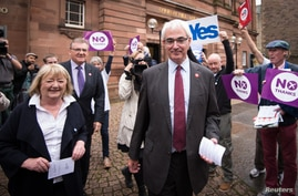 Former Chancellor of the Exchequer and leader of the Better Together campaign, Alistair Darling, walks with his wife Maggie outside the polling station at the Church Hill Theatre in Edinburgh, Scotland, Sept. 18, 2014.