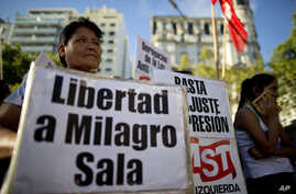 """A woman holds a banner that reads in Spanish """"Free Milagro Sala"""" during a demonstration in support of Argentina's Tupac Amaru social movement leader Milagro Sala, in Buenos Aires, Argentina, Jan. 27, 2016."""