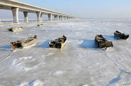 Row boats sit stuck in the ice of the frozen coastal waters of Jiaozhou Bay in Qingdao in eastern China's Shandong province, Jan. 25, 2016.