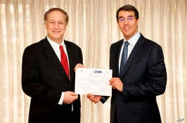 Adam Aron, CEO and President, AMC, left, and His Excellency Dr. Awwad Al-Awwad, Saudi Arabia's Minister of Culture and Information pose with a cinema license to open and operate cinemas in Saudi Arabia on April 4, 2018, in Los Angeles.