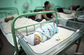 FILE - A newborn rests near his mother at a hospital in Camaguey, Cuba, June 19, 2015. It was in that month that the World Health Organization declared Cuba the first country in the world to eliminate the transmission of HIV and syphilis from mother