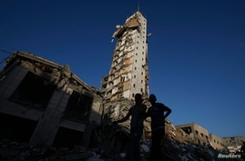 Palestinians stand near the remains of one of Gaza's tallest apartment towers, which witnesses said was hit by an Israeli air strike that destroyed much of it, in Gaza City, August 26, 2014.