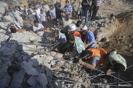 Palestinians search for victims under the rubble of a house which witnesses said was destroyed by an Israeli air strike during an Israeli ground offensive east of Khan Younis in the southern Gaza Strip, July 24, 2014.