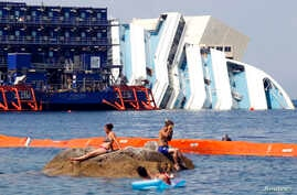People sunbathe in front of the capsized cruise liner Costa Concordia lying surrounded by cranes outside Giglio harbor, Italy, July 17, 2013.