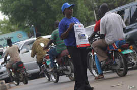 A stream of boda bodas passes a woman holding a poster advertising the launch of a new VOA frequency in Juba in March 2013.