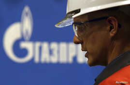 An employee works on pipes made for the South Stream pipeline near a Gazprom logo at the OMK metal works in Vyksa in the Nizhny Novgorod region, April 15, 2014.