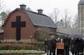 Pallbearers carry the casket of the Rev. Billy Graham past family members as it returns to the Billy Graham Library in Charlotte, N.C., March 1, 2018.