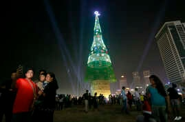A Sri Lankan family takes photographs standing near an enormous artificial Christmas tree as others gather in Colombo, Sri Lanka, Dec. 24, 2016. Sri Lanka has unveiled a towering Christmas tree, claiming to have surpassed the world record for the tal