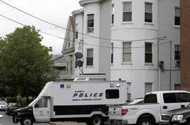 Police vehicles sit in front of a multistoried home in Everett, Mass., being searched by authorities in connection with the fatal police shooting of a man earlier in the day in Boston, June 2, 2015.